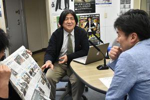 20日付の特集紙面を見ながら説明する中村教諭(中央)=佐賀市のNBCラジオさが