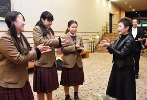 校歌を作詞・作曲した加藤登紀子さん(右)に手話で披露する神埼清明高の生徒たち=佐賀市文化会館