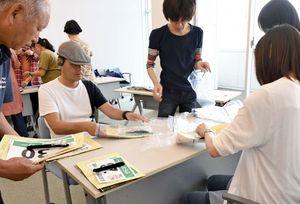 ゼッケンなど備品を袋に詰める虹の松原トライアスロンのボランティアたち=唐津市の大手口センタービル