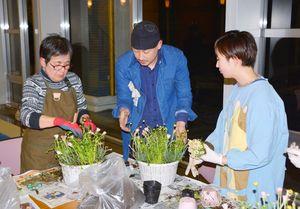 金ケ江太さん(中央)の助言を受け、花苗を植える参加者=有田町の焱の博記念堂