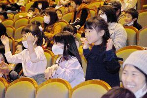 佐賀商高吹奏楽部による演奏で「パプリカ」が流れ、一生懸命踊る子どもたち=佐賀市文化会館
