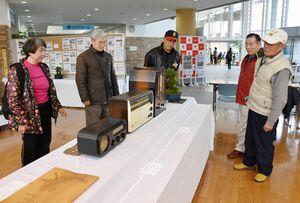 再生した真空管ラジオを前に懐かしそうな卒業生や来場者=唐津市高齢者ふれあい会館りふれ