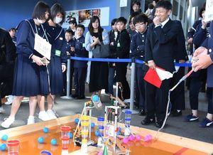 自作のロボットを操作してコップに球を入れる中学生=武雄市の県立宇宙科学館