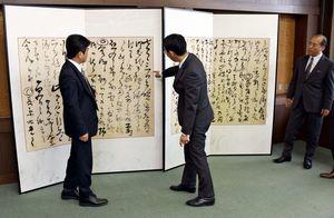 鍋島夏雲日記を表装した屏風を眺める武広町長(左)ら=上峰町役場
