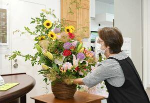 季節の花を取り入れたアレンジメントを設置する生花店の店員=佐賀市役所