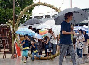 傘を片手に、一礼して茅の輪をくぐる参拝者=佐賀市の佐嘉神社