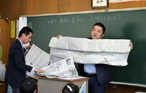 印刷前の紙の大きさを見せる山﨑記者(右)