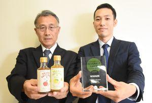 国際的な賞の受賞盾と「シャンティ スウィッチェル」を手にしたカラツスタイルの片渕一暢さん(右)とサガ・ビネガーの右近雅道社長