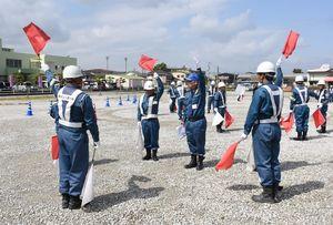 赤と白の手旗で車を誘導する技術を確認する参加者=上峰町役場南側駐車場