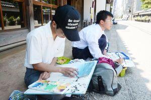 街角に座り込んで絵を描く美術部員ら=佐賀市柳町周辺