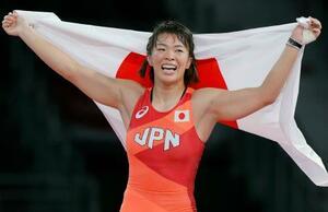 女子57キロ級で優勝し、日の丸を掲げ笑顔の川井梨紗子=幕張メッセ