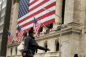 ニューヨーク証券取引所の前をマスク着用で歩く人(ロイター=共同)
