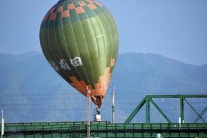 JRバルーン佐賀駅近くで線路に接触して球皮が引っかかった気球=佐賀市の嘉瀬川河川敷