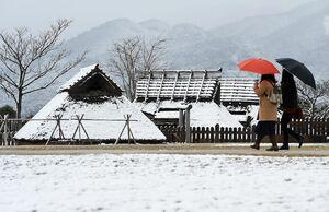「雪化粧」した弥生時代の復元建物=18日朝、吉野ヶ里歴史公園