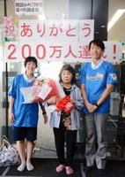 200万人目に訪れた古賀さん(中央)と、祝福するセンターの職員=佐賀市高木瀬の健康運動センター