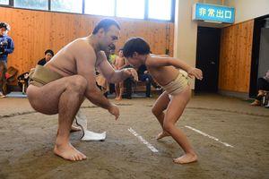 子どもの体当たりを簡単にいなす鳴戸親方=唐津市和多田の唐津市文化体育館