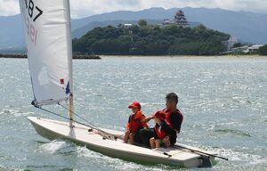 県ヨット連盟が開いたヨット教室。指導員が同乗して、ヨットを楽しむ児童たち=唐津湾