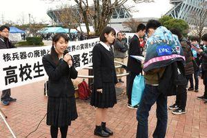核兵器廃絶に向けた署名を呼び掛ける高校生平和大使の藤田裕佳さん(左)ら=鳥栖市のベストアメニティスタジアム周辺