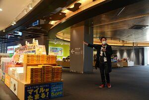 リニューアルした佐賀空港2階の物販エリアを紹介する西村浩さん=佐賀市川副町