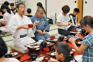 県産食材を使った朝ご飯のおいしさに、笑顔を見せるはなわさん(左)=佐賀市の佐賀城本丸歴史館