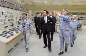 原子炉補助建屋内の中央制御室を視察し、説明を受ける山口知事(中央)。右端は瓜生道明九州電力社長=19日午後、東松浦郡玄海町の玄海原発(代表撮影)