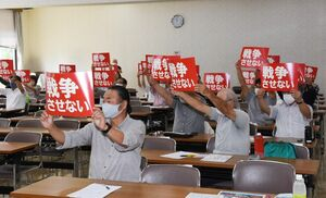 安全保障関連法の廃止を求めて、プラカードを掲げた集会参加者=佐賀市駅前中央の自治労会館