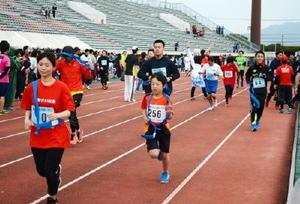 青いたすきをつなぎながらリレーマラソンを楽しむ参加者たち=県総合運動場陸上競技場
