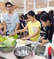 講師のカイムックさん(左)に教わりながら、料理に挑戦する参加者=佐賀市の県国際交流プラザ
