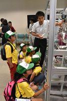 模擬装置を使った温度差発電の説明に聞き入る子どもたち=伊万里市の佐賀大海洋エネルギー研究センター