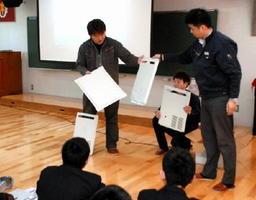 製造した金型をもとに作られた部品を示し、自社の紹介をする青年工業会のメンバーら=佐賀市の佐賀学園高校