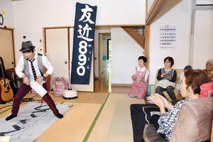 歌いながら書道を披露する友近890(やっくん)さん(左)とパフォーマンスを見つめる利用者ら=佐賀市の宅老所「ひだかの里」