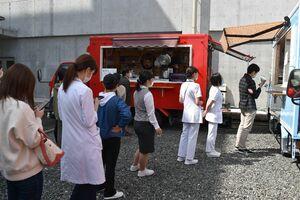 提供される弁当を求め、キッチンカー前に並ぶ好生館職員=佐賀市嘉瀬町の好生館