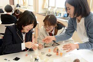 日本の生徒と一緒にネイルチップを楽しく制作する韓国の中高生=佐賀市の佐賀女子高