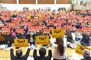 オスプレイに反対するプラカードを掲げる参加者=佐賀市の川副スポーツセンター