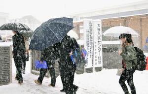 雪が降る中、大学入試センター試験の会場に向かう受験生=14日午前、秋田市