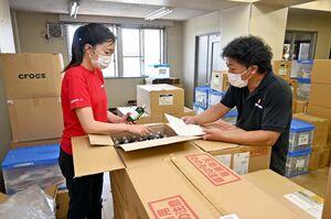静岡県熱海市に送る支援物資を確認する「シビックフォース」の根木佳織代表理事(左)ら=5日午後、佐賀市