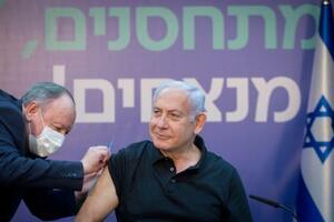 9日、中部ラマトガンの施設でワクチン接種を受けるイスラエルのネタニヤフ首相(ロイター=共同)