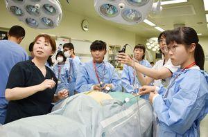 腹腔鏡手術を模擬体験する中高生=伊万里市二里町の山元記念病院