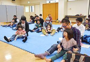 体を動かす遊びなどを通してふれあう父親と子ども=神埼市の千代田町保健センター