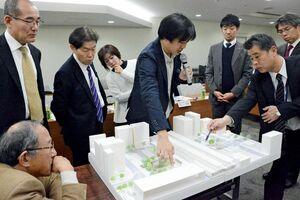 佐賀駅南口の交流広場の整備について、模型を見ながら意見を交わす委員ら=佐賀市役所
