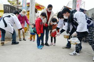 参拝者の足元に灰を振り掛け、無病息災などを願う「灰振り祭り」=唐津市湊の湊疫神宮