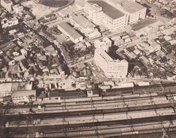 中央やや右寄りの建物が鳥栖ビル。その上方の広大な敷地と建物群は専売公社鳥栖工場(現在のフレスポ鳥栖)、左下は鳥栖駅=1967年11月下旬の鳥栖駅周辺(鳥栖倉庫提供)