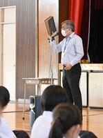 開校当初からの学校や生徒の様子が記録された本を持ち、神埼高の歴史を振り返る原口哲哉校長=神埼市の同校