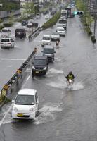 冠水した左車線を避けて、走行する車の列=6日午前8時5分、小城市牛津町の国道34号(写真の一部を画像加工しています)