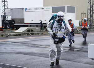 重大事故が発生した想定で、大容量空冷式発電機(奥)から迅速に戻る九電職員=東松浦郡玄海町の玄海原発