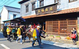 陶磁器店が並ぶ有田の通りを進む牛車(2013年11月、有田観光協会提供)