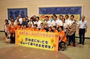 アマチュア吹奏楽団によるミニコンサート後に記念撮影する「認知症の人と家族の会」の会員ら=佐賀市の県庁県民ホール