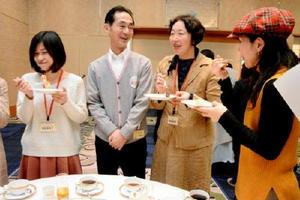 ドーナツを食べながら山村輝治社長(中央)と意見交換する参加者=佐賀市のホテルニューオータニ佐賀