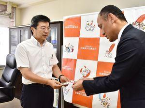 目録を受け取る県共同募金会の伊藤正副会長(左)=佐賀市鬼丸町の同会