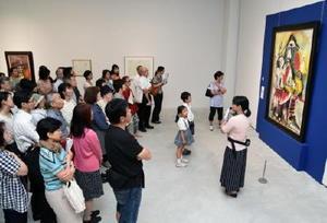 ナイトミュージアムで学芸員の岩永亜季さん(手前右)の作品解説を熱心に聞く来場者=佐賀市の県立美術館